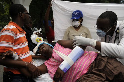 The above photo shows a Haitian woman undergoing surgery in a parking lot without anesthesia. Photo Courtesy: Atlanta Journal Constitution.