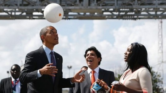 Soccket co-founder, Jessica Matthews, right, shows off the Soccket with President Obama in Tanzania.