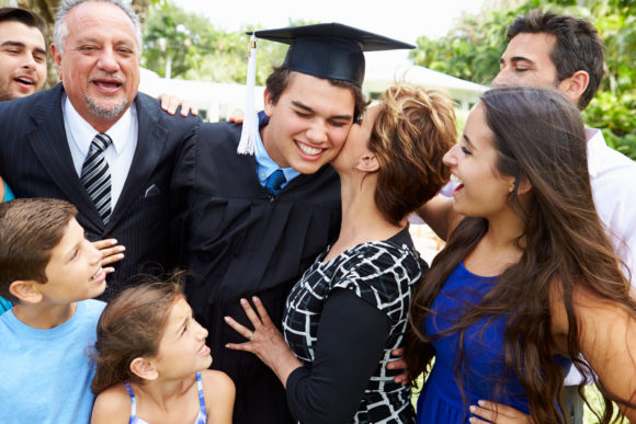 Hispanic Student And Family Celebrating Graduation Smiling