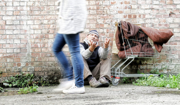 homeless man being ignored by passer by, motion blur on the young woman walking past without looking at the man who has his hands outstretched asking for help.